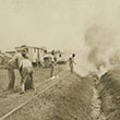 Men burning grass in ditch near railroad tracks